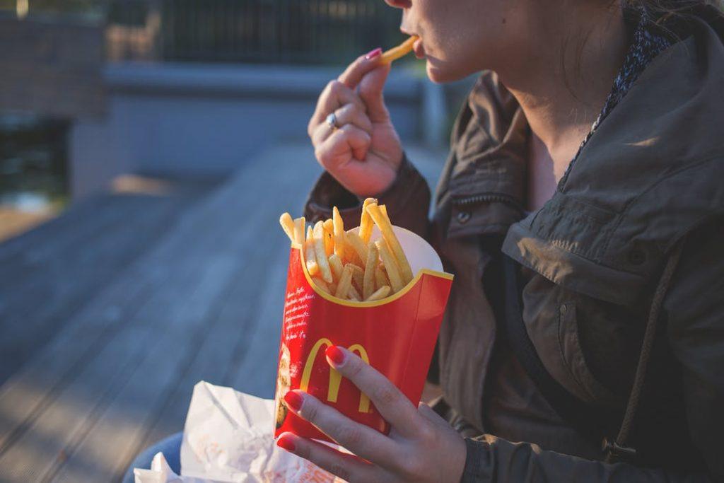 Woman Eating Fast Food Fries
