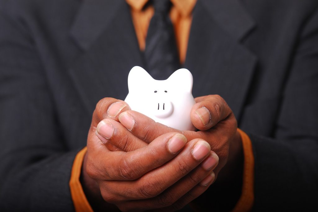 Hands Holding a Small White Piggy Bank