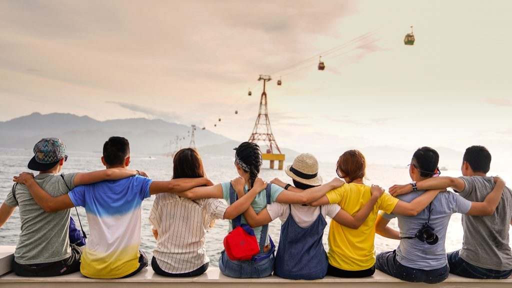 People Seated in a Row with Scenic Sky