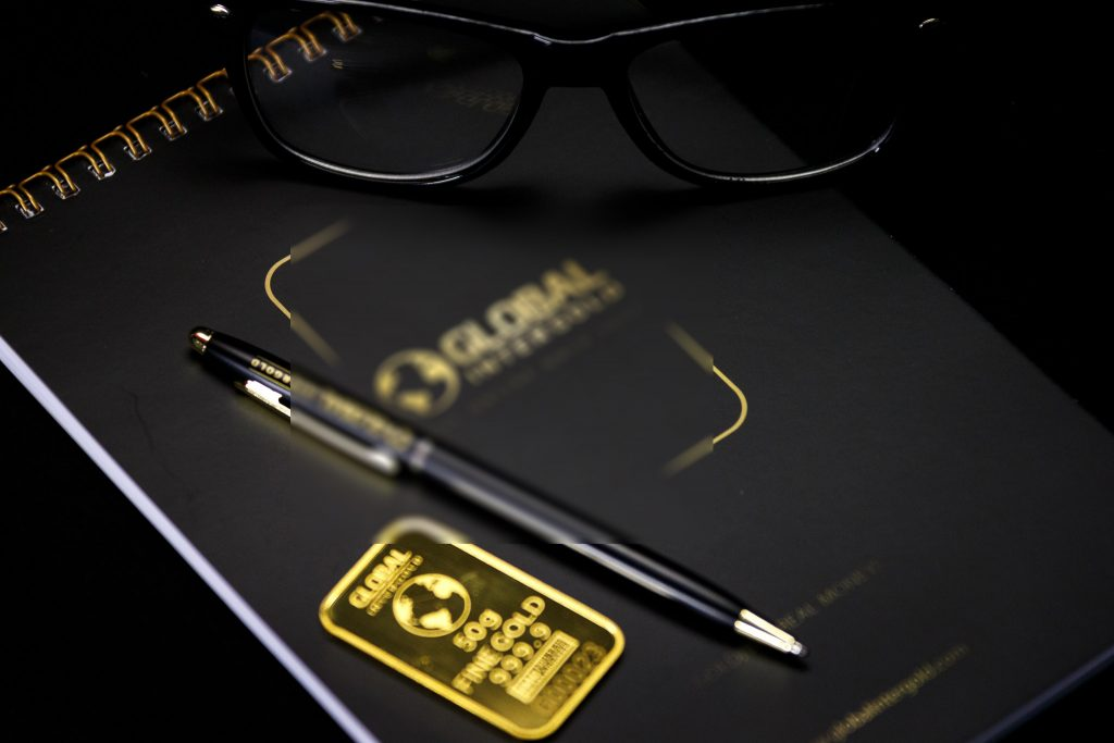 Black and Gold Branded Notebook, Pen, and Glasses