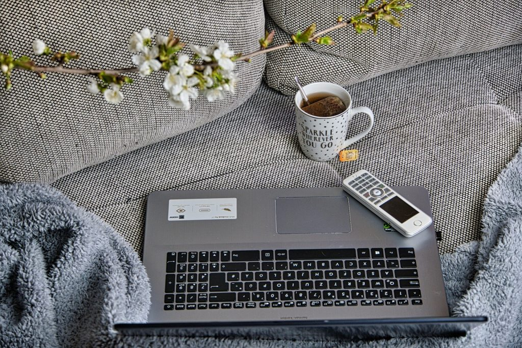 Laptop and Coffee Mug on a Grey Couch