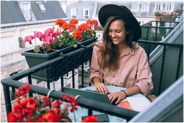 Woman Working on a Balcony Table with Flowers