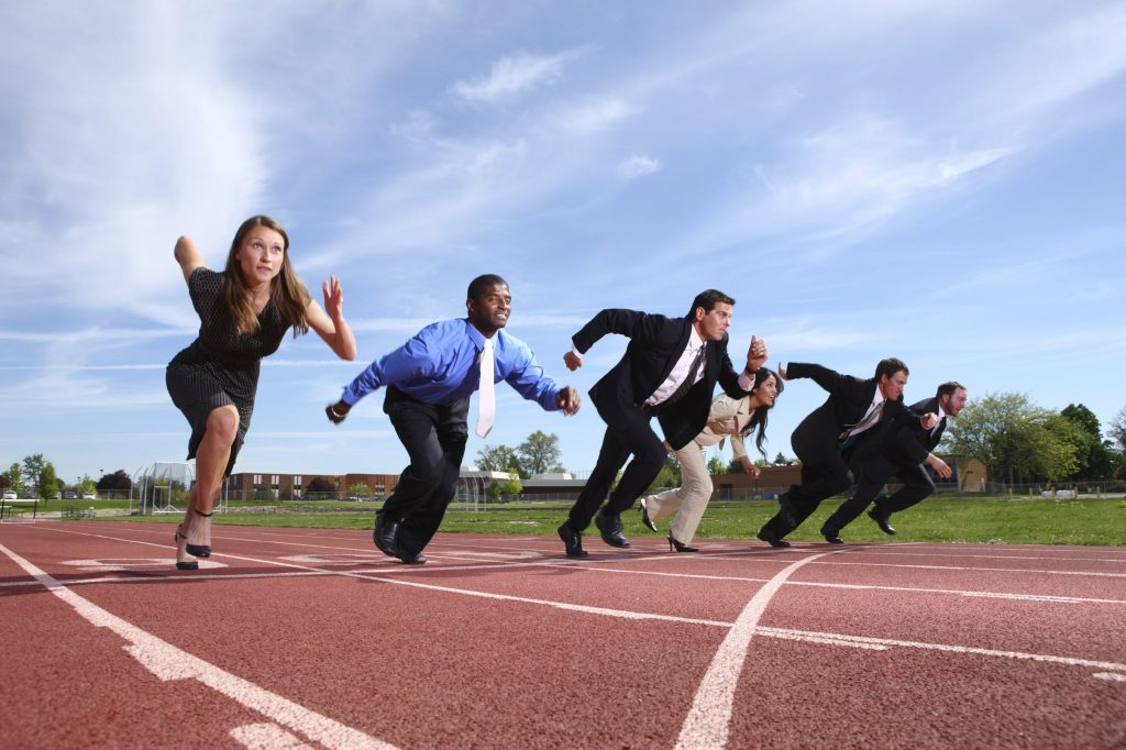 People in Professional Wear Running on a Track