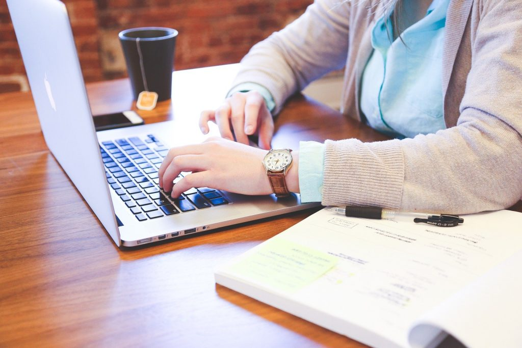 Woman in Pink Cardigan Working on Laptop with Tea Mug and Notebook